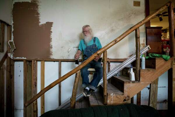 Jack D. Perkins rides down on a stair lift in his flood-damaged home in Conroe. Their home, which is downstream from Lake Conroe, flooded in 1994. When they rebuilt, they put their home on stilts. In the aftermath of Hurricane Harvey, their home flooded again. They are part of a group of homeowners, who live downstream from the Lake Conroe dam, who are suing the San Jacinto River Authority.