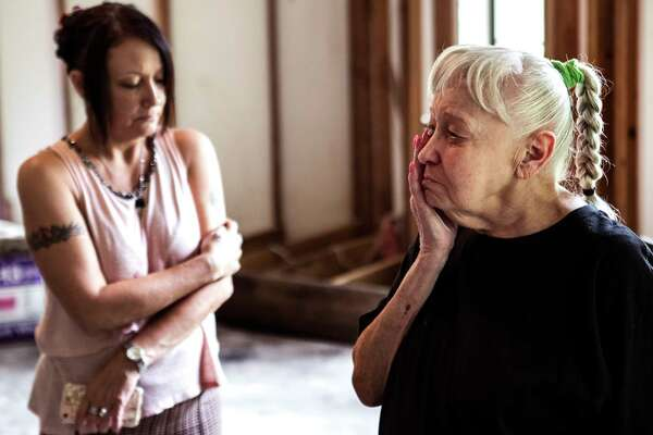 Deryl Thompson, right, and her daughter, Teresa Thompson, reflect on family memories in their now flood-damaged home in Conroe.