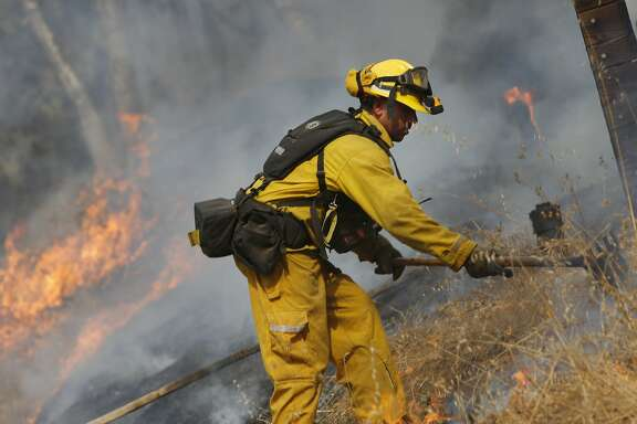 A firefighter works to control a fire  near a bulldozer line created behind homes along Bennett Valley Road as he and other firefighters monitor it 's progress on Wednesday, October 11, 2017 in Santa Rosa, Calif.