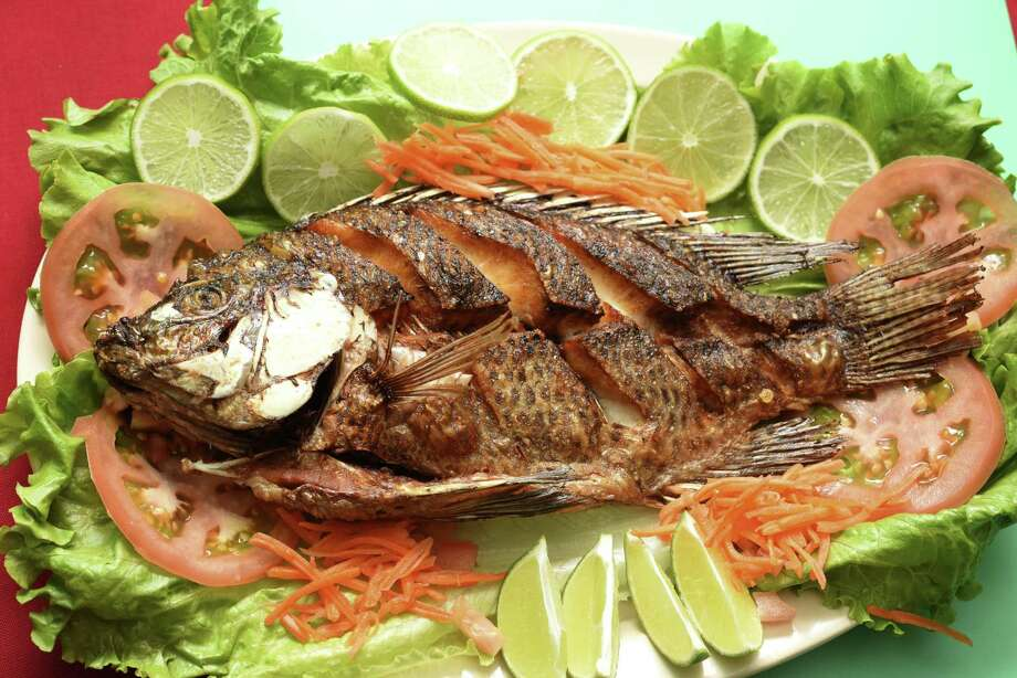 A whole fried tilapia is the centerpiece of the mojarra frita plate at Guajira Cuban Restaurant. Photo: Billy Calzada /San Antonio Express-News / San Antonio Express-News