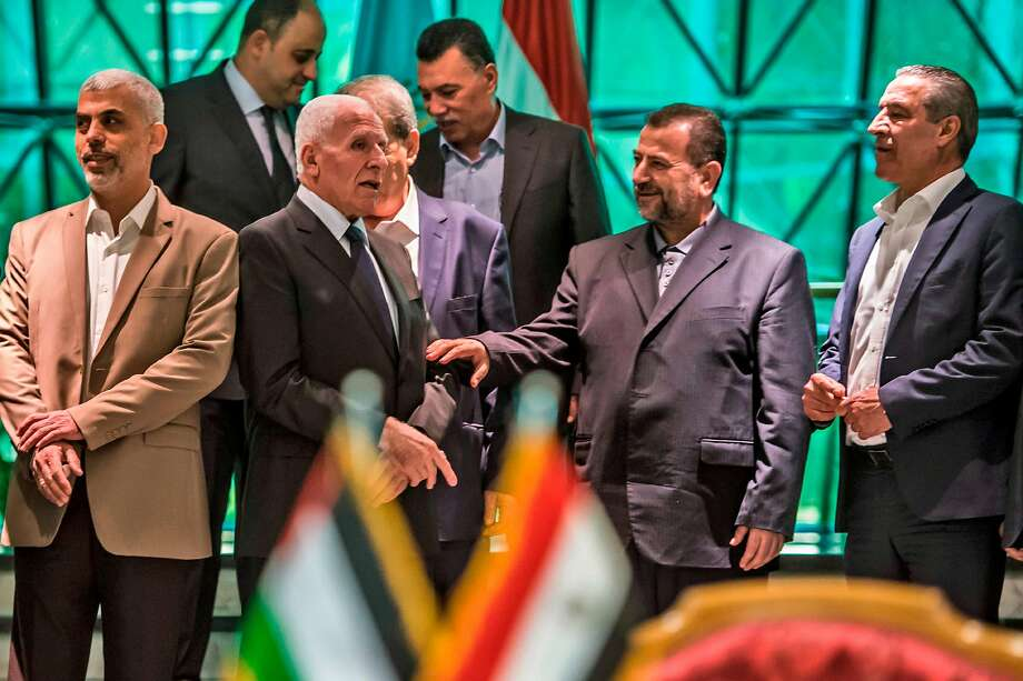 Fatah's Azzam al-Ahmad (C-L) speaks with Hamas' Saleh al-Aruri (C-R) after signing a reconciliation deal in Cairo on October 12, 2017, as the two rival Palestinian movements ended their decade-long split following negotiations overseen by Egypt. Under the agreement, the West Bank-based Palestinian Authority is to resume full control of the Hamas-controlled Gaza Strip by December 1, according to a statement from Egypt's government. / AFP PHOTO / KHALED DESOUKIKHALED DESOUKI/AFP/Getty Images Photo: KHALED DESOUKI, AFP/Getty Images