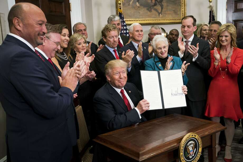 President Trump signs an executive order that clears the way for potentially sweeping changes in health insurance. Photo: DOUG MILLS, NYT