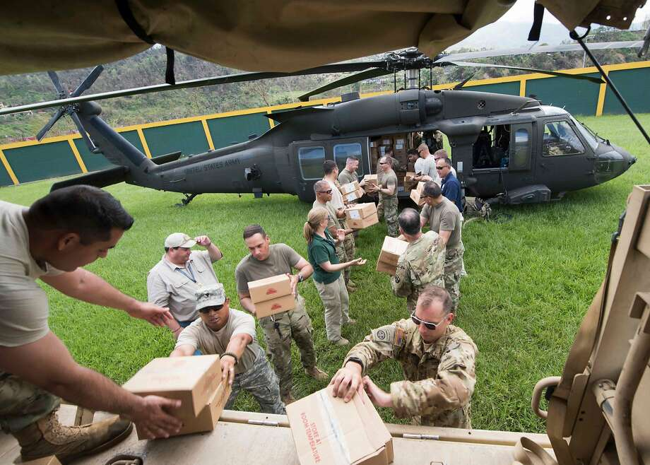 Puerto Rico National Guard soldiers unload a helicopter carrying relief supplies in Jayuya. Most residents have no power or clean drinking water. Photo: NYT