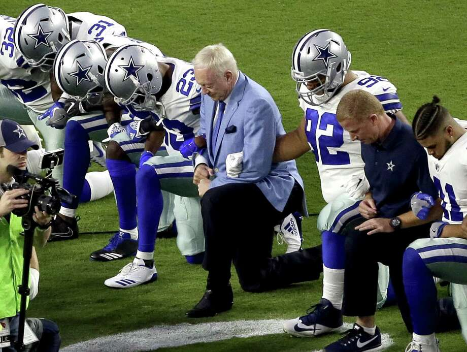 """In this Monday, Sept. 25, 2017, file photo, the Dallas Cowboys, led by owner Jerry Jones, center, take a knee prior to the national anthem and an NFL football game against the Arizona Cardinals, in Glendale, Ariz. ESPN anchor Jemele Hill has been suspended by the network for two weeks for making political statements on social media. Hill, who is African-American, received criticism from the network last month after referring to President Donald Trump as a """"white supremacist."""" On Monday, Oct. 9, 2017, Hill targeted Jerry Jones, after the Dallas Cowboys owner stated that players who disrespect the flag would not play for his team. Photo: Matt York /Associated Press / Copyright 2017 The Associated Press. All rights reserved."""