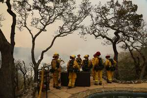 Firefighters during a briefing on how to approach the Norrbom fire burning in the valley below them in Sonoma County, Calif., Oct. 11, 2017. Fires continued to burn out of control across California on Wednesday, with at least 21 people confirmed dead, several hundred unaccounted for, and thousands of buildings destroyed or damaged. (Jim Wilson/The New York Times)