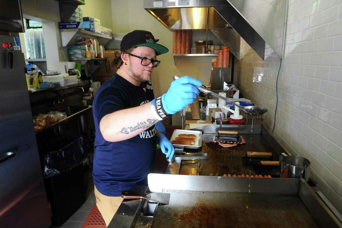 Employee Ben Campo ladles some secret sauce onto the grill during Walter's Hot Dogs first day open in Commons Park in the Harbor Point area of Stamford, Conn. on Thursday, Oct. 12, 2017.