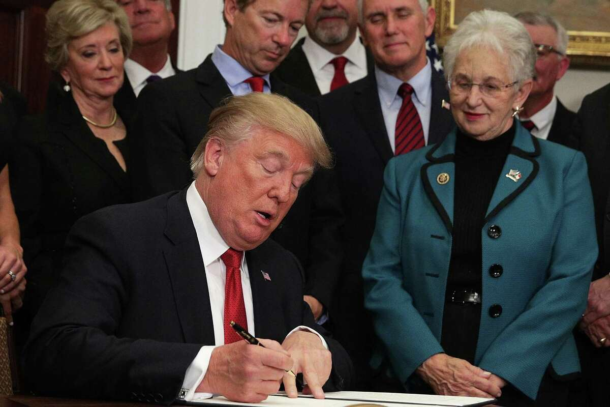 """WASHINGTON, DC - OCTOBER 12: U.S. President Donald Trump signs an executive order as Sen. Rand Paul (R-KY), Vice President Mike Pence, and Rep. Virginia Foxx (R-NC) look on during an event in the Roosevelt Room of the White House October 12, 2017 in Washington, DC. President Trump signed the executive order to loosen restrictions on Affordable Care Act """"to promote healthcare choice and competition."""" (Photo by Alex Wong/Getty Images)"""