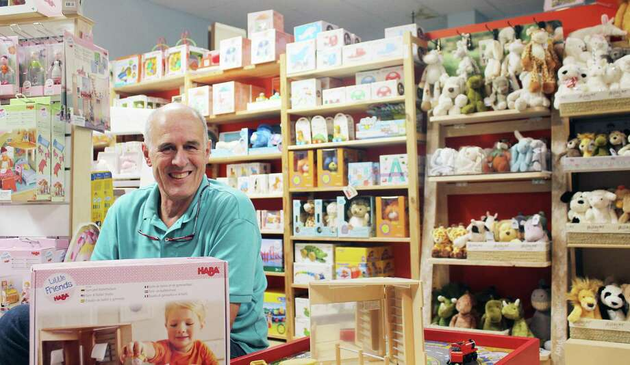 Darien Toy Box owner Bill Jensen sits at a play table in his store on Monday in Darien. Photo: Darien News / Contributed Photo / Darien News