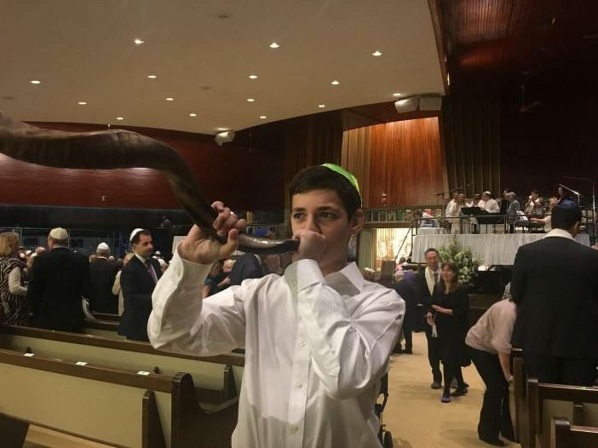 Jeremy Young, 13, blows the shofar after Yom Kippur services at Temple Beth El.