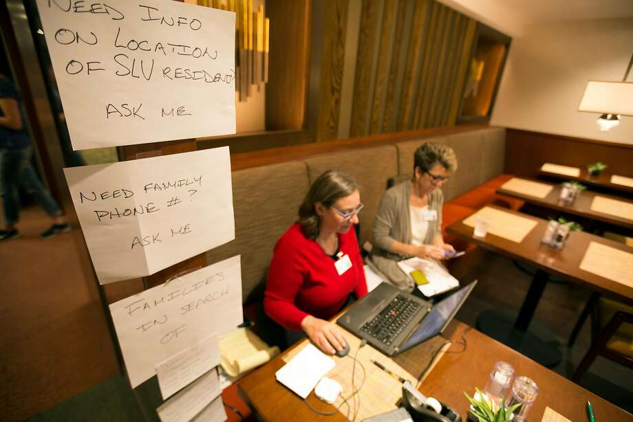 Laura Darling, left, senior director of communications and spiritual care, and Katharine Miller, exeuctive director of the Episcopal Senior Communities Foundation, review the list of evacuees from the fires in Santa Rosa, Calif. now staying at St. Paul's Towers, Wednesday, Oct. 11, 2017 in Oakland, Calif. More than 60 evacuees have been relocated to the facility as fires continue to rage through the North Bay. Photo: D. Ross Cameron, Special To The Chronicle