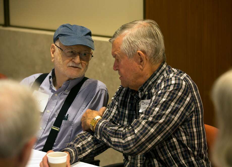 Gus Haas, 90, left, and Barney Johnson, 85, both forced to flee the fires in Santa Rosa, Calif. commiserate with their fellow evacuees at St. Paul's Towers in Oakland on Wednesday. More than 60 evacuees have been relocated to the facility as fires continue to rage through the North Bay. Photo: D. Ross Cameron, Special To The Chronicle