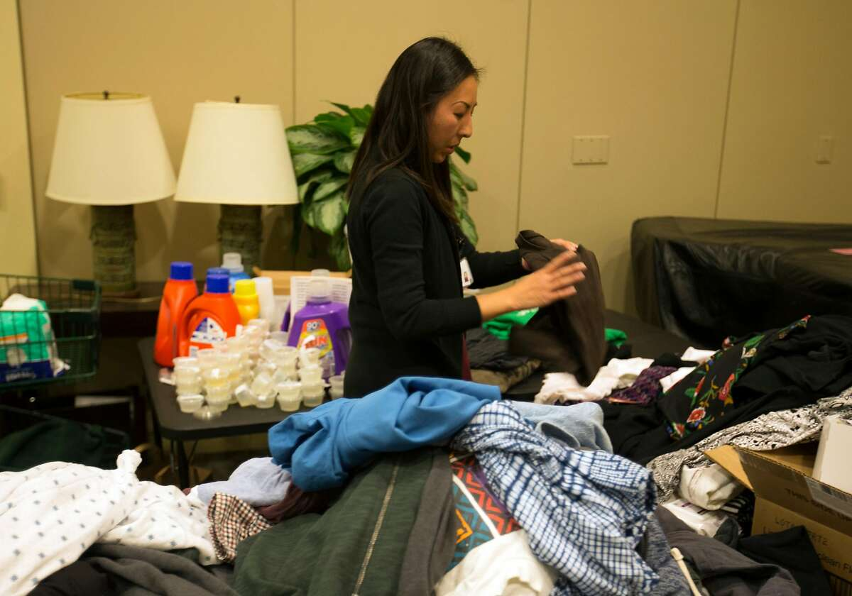 Connie Yuen sorts and organizes donations intended for evacuees from the fires in Santa Rosa, Calif. who are now staying at St. Paul's Towers, Wednesday, Oct. 11, 2017 in Oakland, Calif. More than 60 evacuees have been relocated to the facility as fires continue to rage through the North Bay.