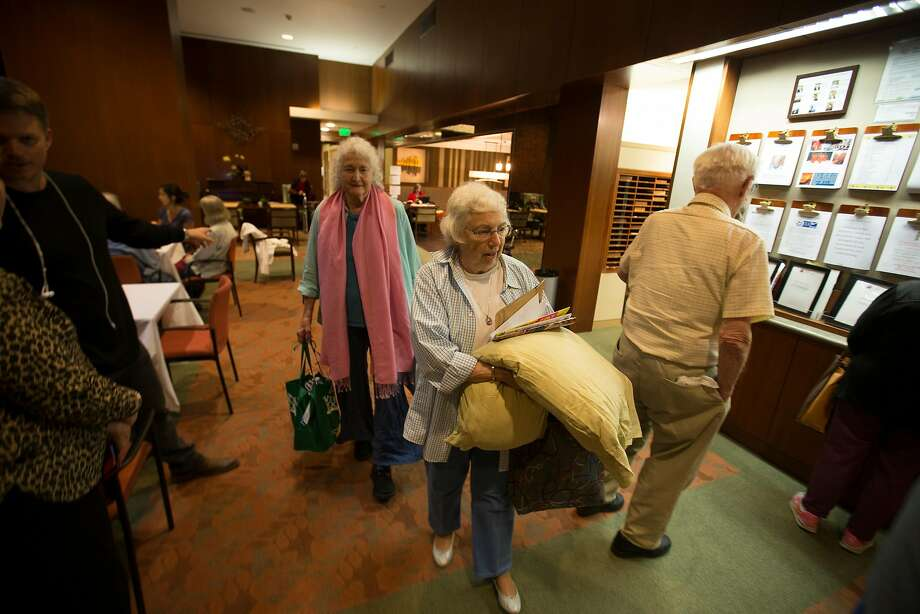 Judith Smith leads the way for her guest, Rebecca Fuller of Santa Rosa, at St. Paul's Towers in Oakland in October. More than 60 evacuees were relocated to the facility during the North Bay wildfires. Photo: D. Ross Cameron, Special To The Chronicle