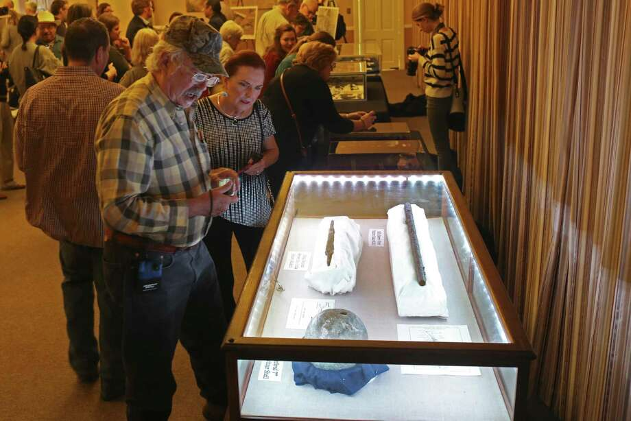 """Don Mathis and Patricia Seidenberger check out artifacts at the Alamo, Thursday. The artifacts were among 150 items on display — most for the first time to the public — as part of a one-day exhibition in celebration of Texas Archeology Month. In the case are clockwise from top left, a Brown Bess India Pattern Musket bayonet, a First Pattern Rifle Baker Rifle barrel and a unfired 7"""" Howitzer shell. Photo: Jerry Lara /San Antonio Express-News / © 2017 San Antonio Express-News"""