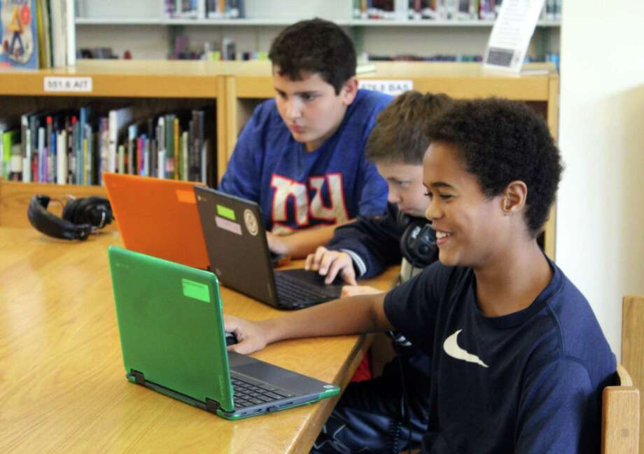 Anderson Campbell and his fellow sixth-grade students on their Chromebooks in the Middlebrook School Library. Photo: Stephanie Kim / Hearst Connecticut Media