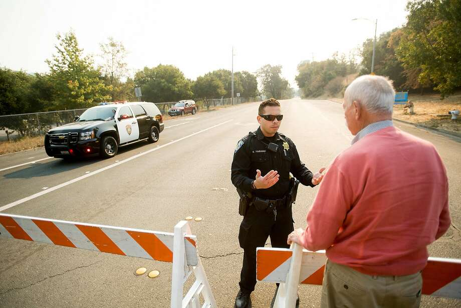 BART police officer Trabanino mans a Tubbs fire checkpoint on Bennett Valley Rd. in Santa Rosa, Calif. on Thursday, Oct. 12, 2017. He was telling a evacuee that the area is still closed to residents. Photo: Noah Berger, Special To The Chronicle