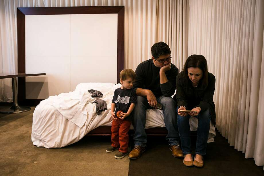 From the left, Luciano Tristan and Julia Harkins watch the Facebook Live morning updates from the Sonoma County Sheriff office on their phones in a meeting room where the family stayed at the Clift Hotel in San Francisco, Calif. Thursday, October 12, 2017. The family left their home in Sonoma on Tuesday when smoke from the fire became a concern for their one-year-old son, Luca Tristan. They found refuge at Clift Hotel, which managed to convert the meeting room into a bedroom for the family to stay. Photo: Mason Trinca, Special To The Chronicle