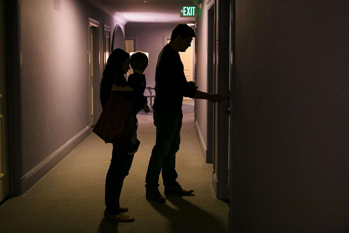 Julia Harkins holds herone-year-old son, Luca Tristan, as Luciano Tristan enters into a meeting room where the family spent the night at Clift Hotel in San Francisco, Calif. Thursday, October 12, 2017.