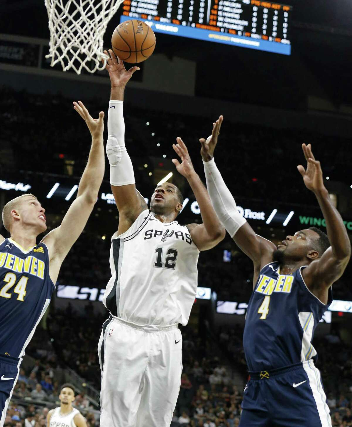 San Antonio Spurs' LaMarcus Aldridge shoots between Denver Nuggets?• Mason Plumlee (left) and Paul Millsap during first half action of their preseason game held Sunday Oct. 8, 2017 at the AT&T Center.