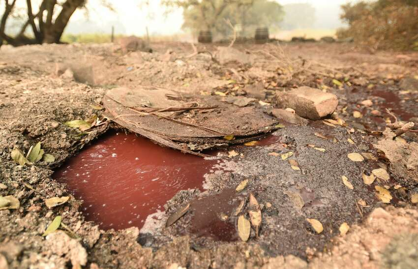 A boiling river of wine flows underneath smoldering debris at the Paradise Ridge Winery in Santa Rosa, California on October 10, 2017. Firefighters battled wildfires in California's wine region on Tuesday as the death toll rose to 15 and thousands were left homeless in neighborhoods reduced to ashes.