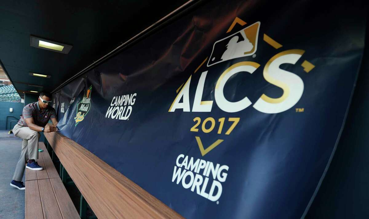 Houston Astros Coordinator, Creative Production, Larry Provitt, works on getting the new ALCS signage up in the dugouts during workouts at Minute Maid Park, Thursday, Oct. 12, 2017, in Houston , ahead of Game 1 of the ALCS.