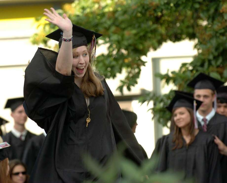 Fairfield Warde High School graduate Lillian Gilbert waves to friends and familiy as she goes up for her diploma. Photo: Christian Abraham / Connecticut Post