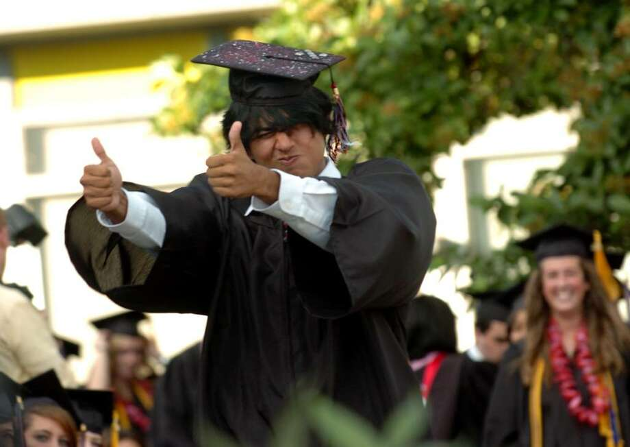 Graduate David Almazan gives the thumbs up sign to Headmaster James Coyne for pronouncing his name correctly, during Fairfield Warde's 6th Annual Commencement Exercises in Fairfield, Conn. on Thursday June 24, 2010. Photo: Christian Abraham / Connecticut Post
