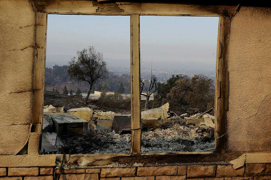 An exterior window frames a home destroyed by fires in Santa Rosa, Calif., Thursday, Oct. 12, 2017. Gusting winds and dry air forecast for Thursday could drive the next wave of devastating wildfires that are already well on their way to becoming the deadliest and most destructive in California history. (AP Photo/Jeff Chiu) Photo: Jeff Chiu, Associated Press
