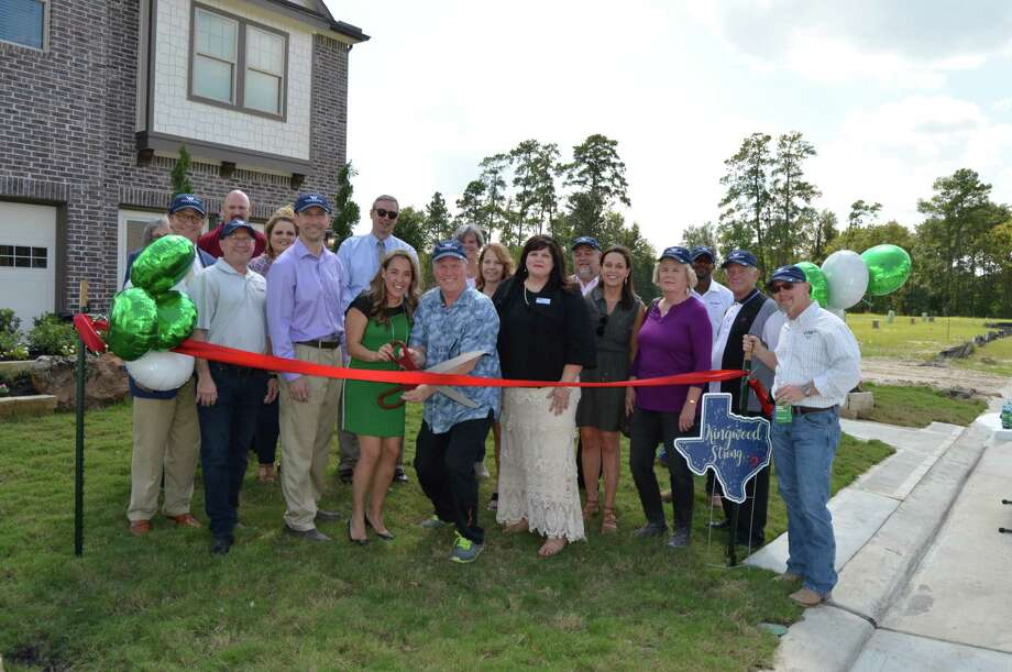 Kingwood Chamber of Commerce president Sparky Nolan gets ready to cut the ribbon at the ribbon cutting ceremony on Friday, Sept. 22, for Woodridge Townhomes being built by Chesmar Homes in Woodridge Forest. Photo: Photo Provided ByLinda Dalton Marketing
