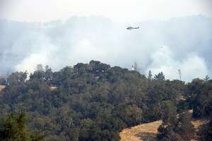 A helicopter drops water on Pocket Fire as it approaches homes in the Vineyard Development in Sonoma County outside of Geyserville, Calif., on Wednesday, Oct. 11, 2017. (Paul Kitagaki Jr. /The Sacramento Bee via AP)