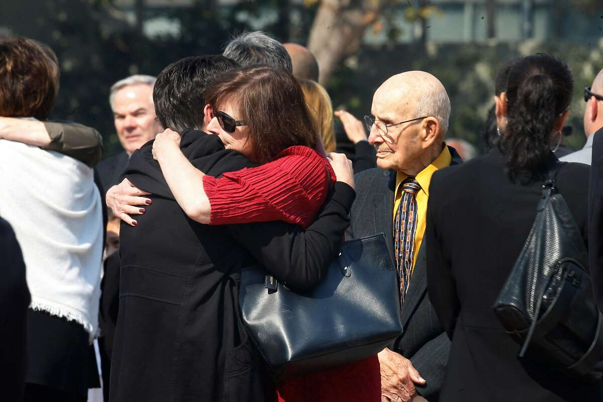 Friends and family hug after funeral services at St. Mary's Cathedral on Thursday, October 12, 2017, in San Francisco, Calif., for Stacee Etcheber. Members of the Las Vegas Metropolitan Police Department enter funeral services for Stacee Etcheber at St. Mary's Cathedral on Thursday