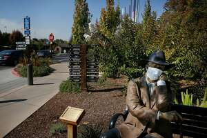 """""""Sidewalk Judge"""" wears a facemask as it sits on a bench in front of the Community Center on Thursday, October 12, 2017 in Yountville, Calif."""