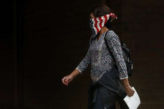 A woman walks past a store wearing a bandana as a mask to protect herself from the smoke Oct. 9, 2017 in Napa, Calif. A fire tore through the area on the evening of Oct. 8, destroying properties and vineyards.