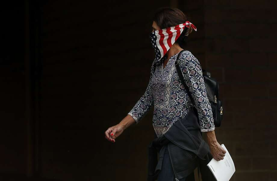A woman walks past a store wearing a bandana as a mask to protect herself from the smoke Oct. 9, 2017 in Napa, Calif. A fire tore through the area on the evening of Oct. 8, destroying properties and vineyards. Photo: Leah Millis / The Chronicle