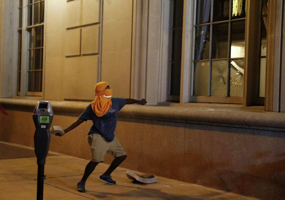 A man throws a rock into a window as demonstrators march in response to a not guilty verdict in the trial of former St. Louis police officer Jason Stockley in St. Louis. Readers continue to discuss the kneeling controversy in the NFL, which emerged as a protest against what players viewed as racial injustice perpetrated by police officers throughout the country. Photo: Jeff Roberson /Associated Press / Copyright 2017 The Associated Press. All rights reserved.