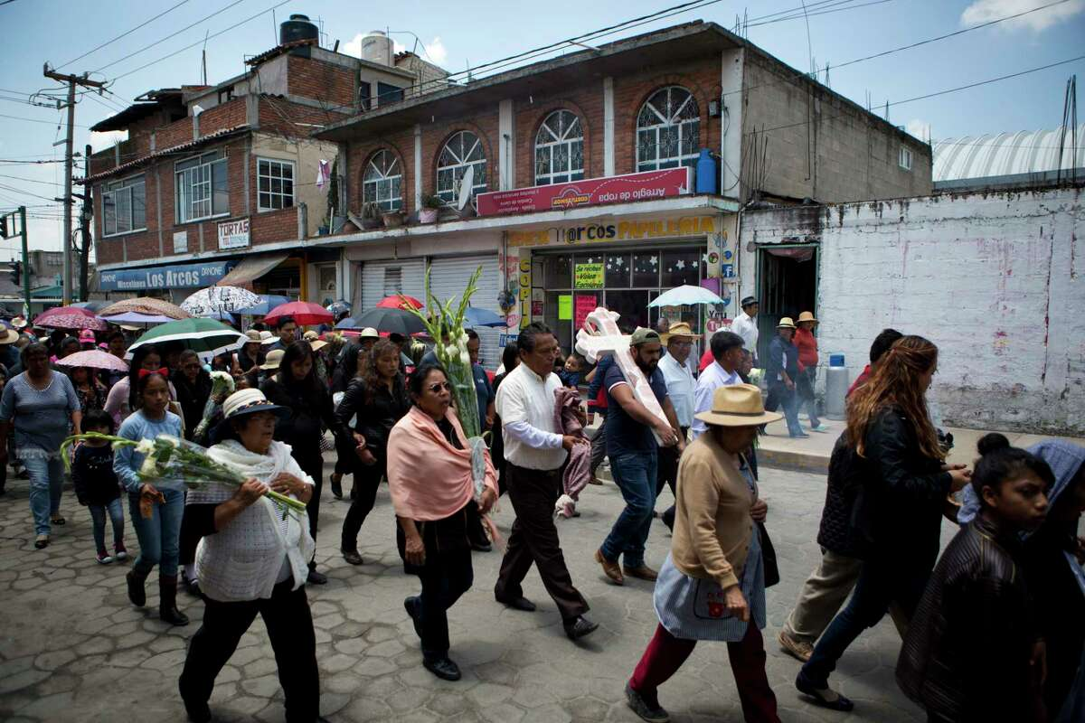 In this Aug. 18, 2017 photo, family and friends walk in procession from the church to the cemetery carrying a cross anointed with holy water to mark the grave of murdered doctor and mother Jessica Sevilla Pedraza, 29, in Villa Cuauhtemoc, Mexico state. Many violent crimes such as disappearances often go unreported and unpunished, and the State of Mexico is widely considered ground zero for killings of women in the country today. (AP Photo/Rebecca Blackwell)
