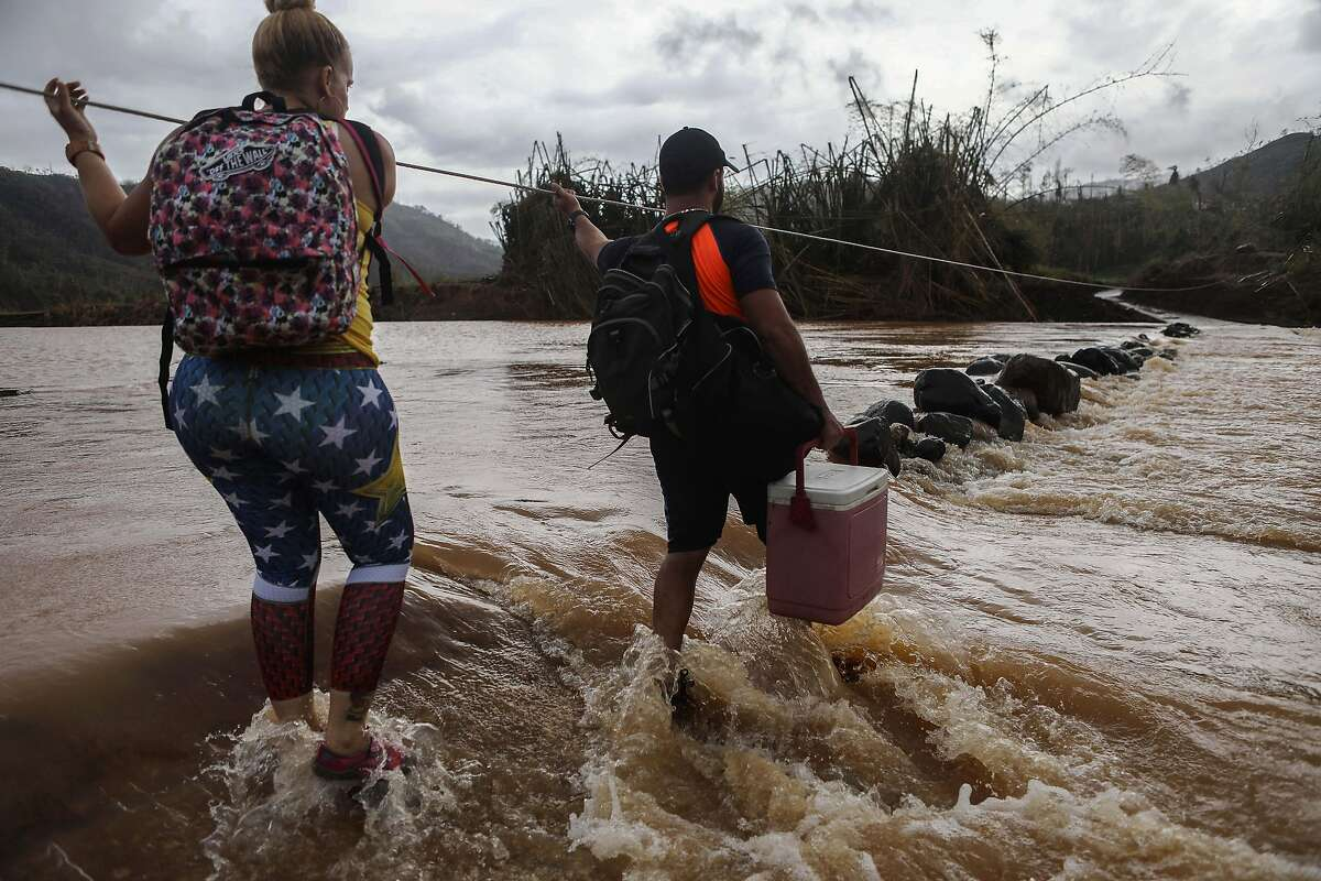 SAN LORENZO, PUERTO RICO - OCTOBER 06: People use a rope line to cross the San Lorenzo de Morovis river, to deliver food and supplies to relatives, more than two weeks after Hurricane Maria hit the island on October 6, 2017 in San Lorenzo, Puerto Rico. Flooding from the hurricane destroyed the bridge and San Lorenzo residents are forced to cross the river on foot or in 4 x 4 vehicles. Less than 11 percent of Puerto Ricans have electricity currently and only 42 percent have working phones. Puerto Rico experienced widespread damage including most of the electrical, gas and water grid as well as agriculture after Hurricane Maria, a category 4 hurricane, swept through. (Photo by Mario Tama/Getty Images)
