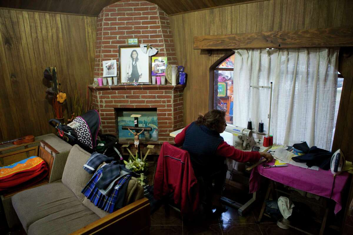 In this Aug. 23, 2017 photo, Juana Pedraza sits next to a small altar in honor of her oldest daughter Jessica, who was murdered at age 29, as she sews school uniforms to order at her home in Villa Cuauhtemoc, Mexico state. Pedraza raised her five daughters to be confident that they are equal to men and that nobody can hold them back. Now tasked with raising her grandson, Jessica's son Leon, she said she's focusing on the other side of the equation: Schools teach kids to read and write, but other values are instilled at home. (AP Photo/Rebecca Blackwell)