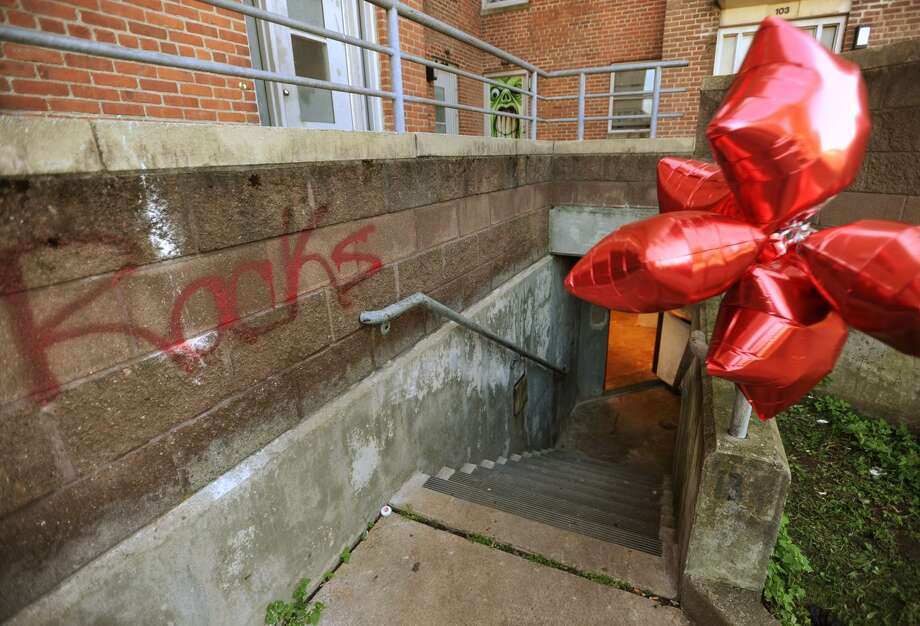 """A stairway to the basement of Charles Greene Homes housing project Building No.1 is marked with the spray painted name """"Racks"""", and a bunch of helium balloons where Jeri """"Racks"""" Kollock, 18, was shot and killed on Wednesday. At left, Chickie Bush, of Bridgeport, stands outside the building. Photo: Brian A. Pounds / Hearst Connecticut Media / Connecticut Post"""