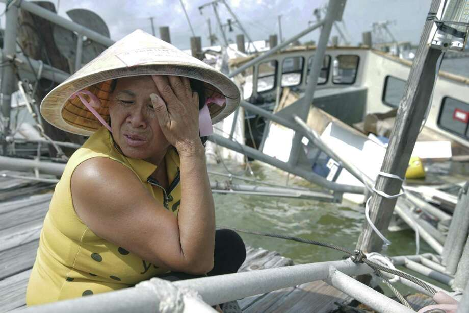 A distraught Le An Thi holds back tears while overlooking her family's  shrimping boat as it rests in the water after sinking at the dock as Rockport tries to recover from Hurricane Harvey devastation on September 26, 2017.  The family of the owner, all Vietnamese immigrants, had just invested $75,000 three days prior to seeing it destroyed. Photo: Tom Reel, Staff / San Antonio Express-News / 2017 SAN ANTONIO EXPRESS-NEWS
