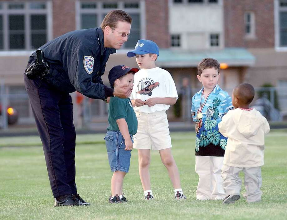 """Middletown police officer David Beauchemin performs a little crowd control during last June's Middletown High School graduation. """"Working with kids was the best part of the job,"""" said Beauchemin.................TW photo................021904"""