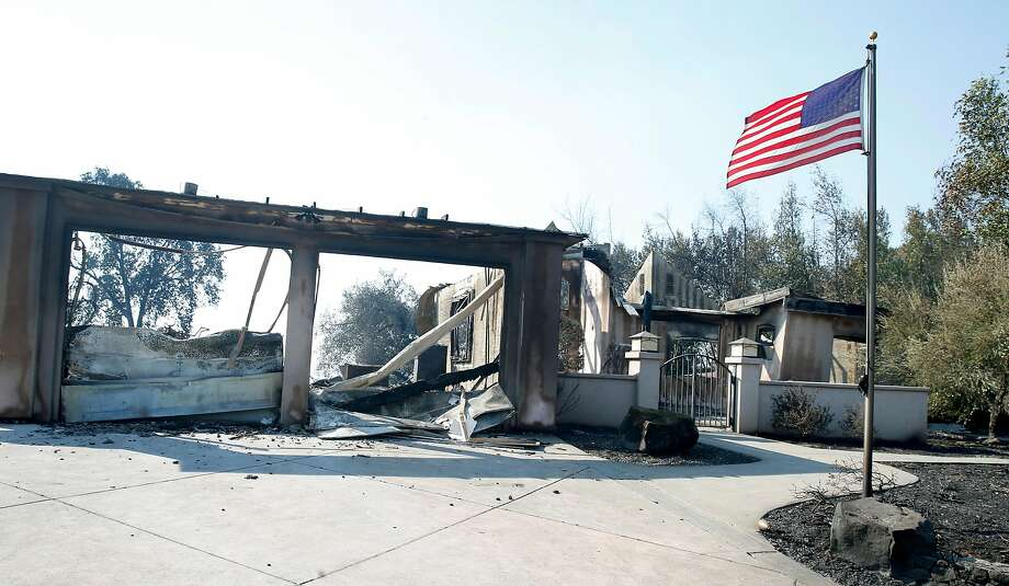 A flag undamaged in Monday's firestorm continues to fly in front of home destroyed by the blaze in Santa Rosa. Photo: Paul Chinn, The Chronicle
