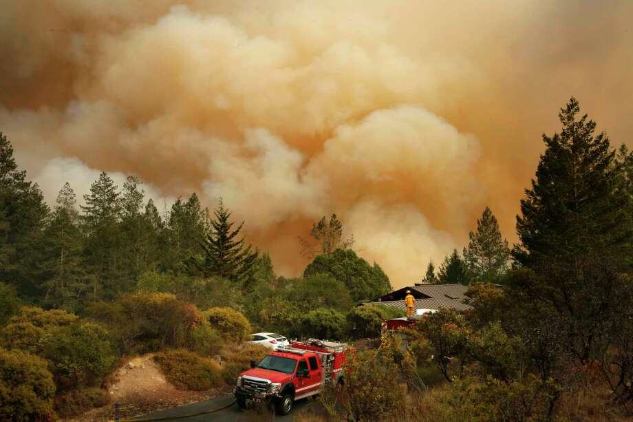"Firefighters keep a close watch on a fire in Santa Rosa, Calif. Efforts have focused on ""life safety"" rather than extinguishing the blazes, partly because flames were shifting and targeting communities without warning. Photo: Michael Macor, Staff / ONLINE_YES"