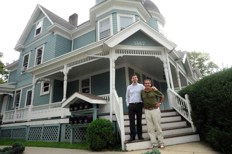 Maurice Nizzardo, center right, and son Cody Nizzardo pose in front of the blue Queen Anne-style house on Summer Street in Stamford, Conn. on Wednesday, Oct. 11, 2017. The old building now has offices on the first two floors and an apartment on the third. Photo: Michael Cummo / Hearst Connecticut Media / Stamford Advocate