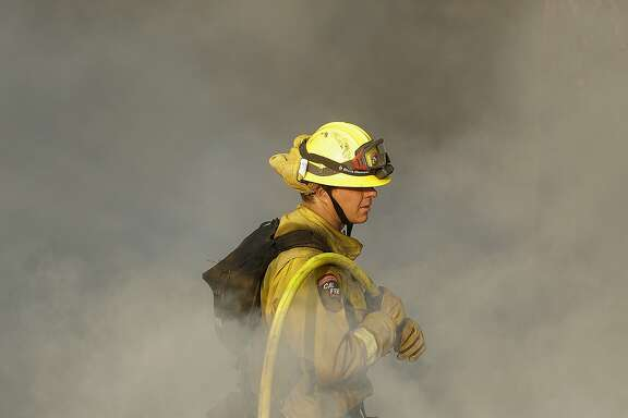 A Cal Fire firefighter works on hot spots on a hill in the Oakmont area of Santa Rosa, Calif., Thursday, Oct. 12, 2017. Gusting winds and dry air forecast for Thursday could drive the next wave of devastating wildfires that are already well on their way to becoming the deadliest and most destructive in California history. (AP Photo/Jeff Chiu)