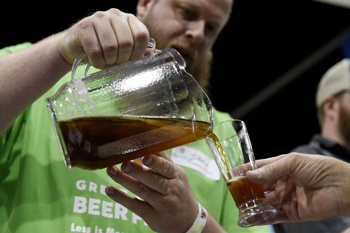 Dustin Powers pours the Red Irish Hart for an attendee at Castle Rock Beer Company's booth during the Great American Beer Festival at the Colorado Convention Center in Denver, Colorado on October 7, 2016.