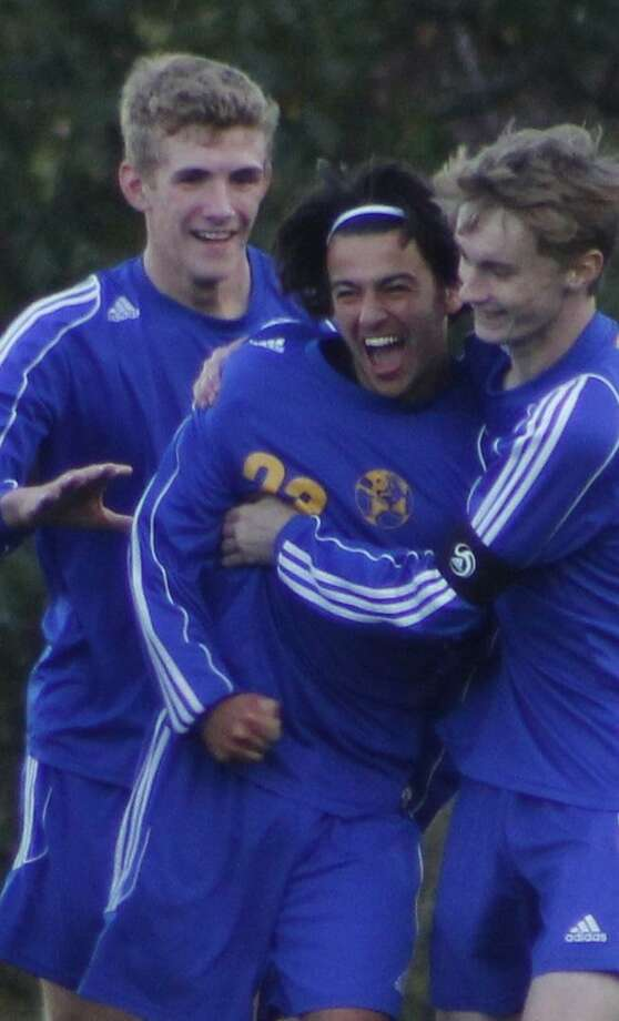 Newtown's Adam Farley, center, celebrates with teammates Evan Eggleston, left, and Brendan O'Hara, right, after scoring the lone goal in the boys soccer game against Barlow at Joel Barlow High School in Redding Oct. 12, 2017. Photo: Richard Gregory / Richard Gregory