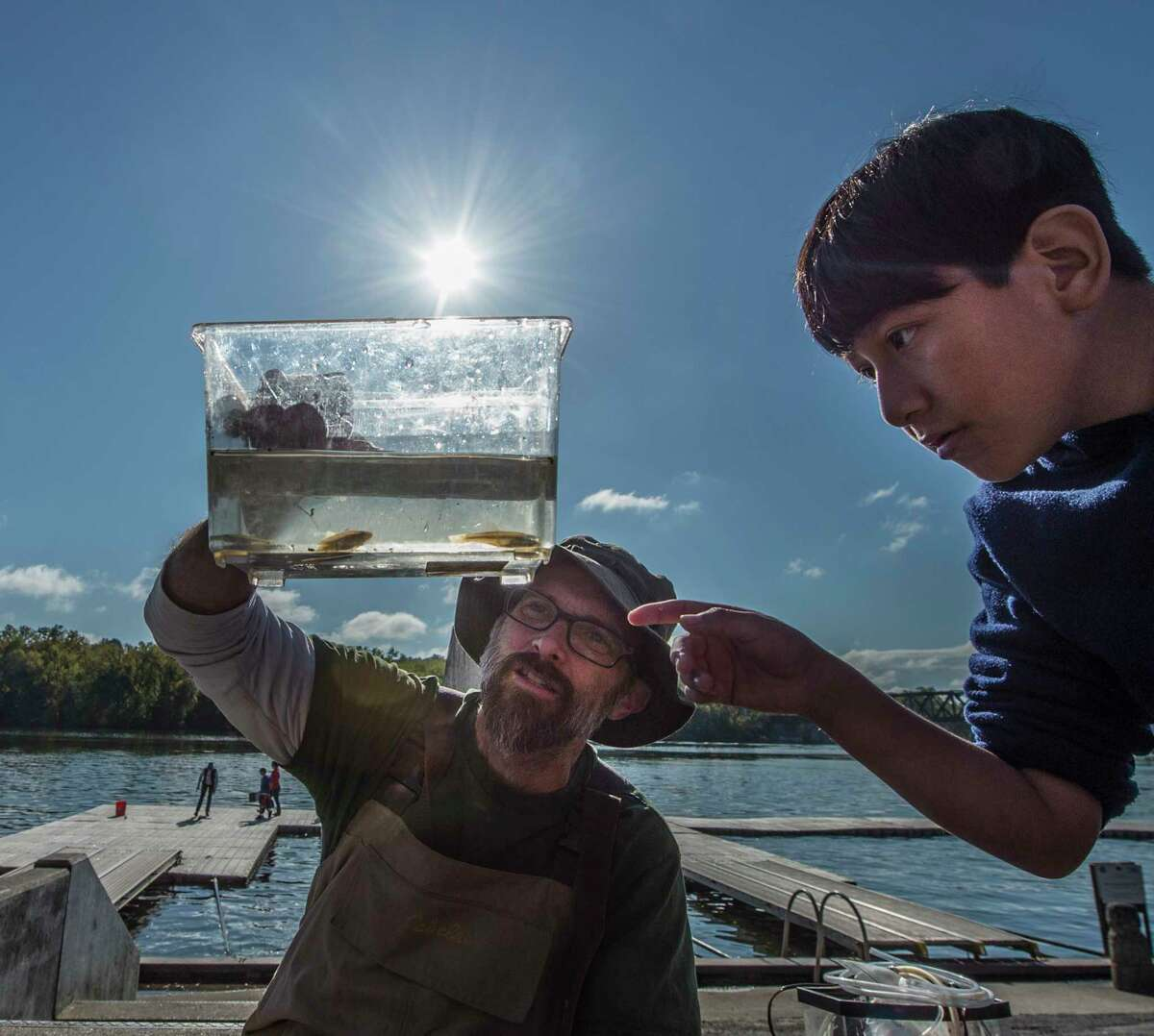 """Sean Madden, of the DEC works with student Edwin Caquana Lemi, 9, as they identify fish caught in the Hudson River and were joined by other students from the Albany Montessori Magnet School at the Corning Preserve to become """"scientists for the day"""" in the 15th annual Day in the Life of the Hudson and Harbor Thursday Oct. 12, 2017 in Albany, N.Y. Students up and down the Hudson River spend their time collecting and analyzing real data from the field during hands-on exploration of the Hudson River Estuary. (Skip Dickstein/Times Union)"""