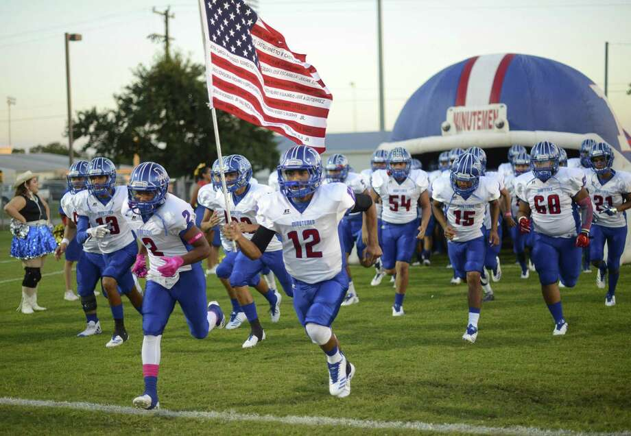 The Memorial Minutemen take the field for their District 28-5A high school football matchup against Brackenridge at the SAISD Sports Complex on Oct. 12, 2017. Adrian Urdiales carries the flag. Photo: Billy Calzada /San Antonio Express-News / San Antonio Express-News