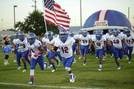 The Memorial Minutemen take the field for their District 28-5A high school football matchup against Brackenridge at the SAISD Sports Complex on Oct. 12, 2017. Adrian Urdiales carries the flag.